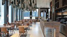 """Im Erdgeschoss des Geschäftshauses """"Am Hamburger Bahnhof"""" in Berlin befindet sich ein Restaurant und Café. In dem hellen, hohen Raum mit seinen bodentiefen Fenstern sorgte der Restaurantinhaber für einen kontrastreichen Stil: warmes Holz und kalter Beton, an der Decke zylinderförmige Filzkörper, die eine angenehme Akustik gewährleisten, und glatter, weißer Terrazzo am Boden."""