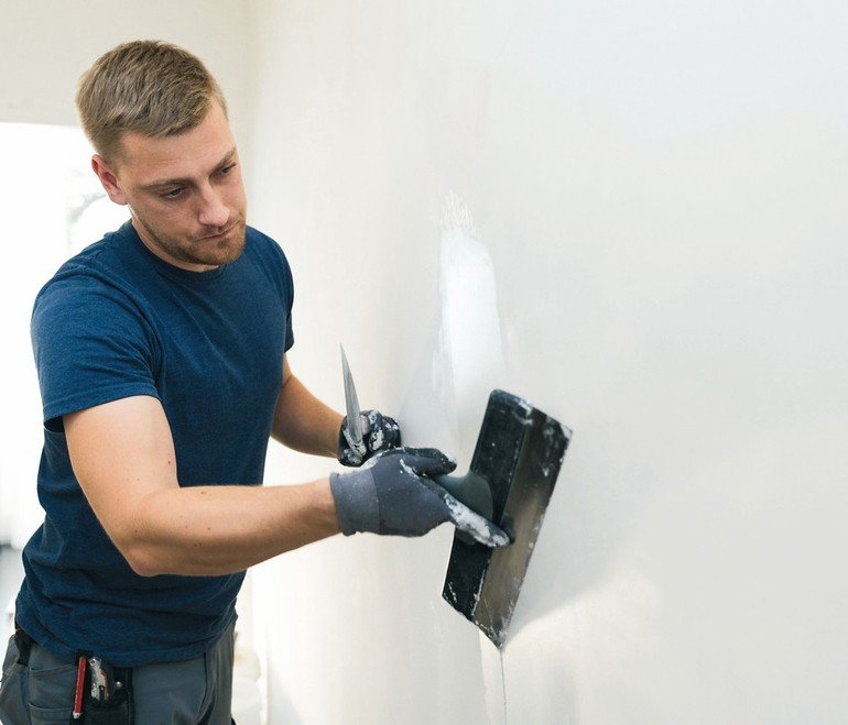 home_improvement_-_construction_worker_with_plastering_tools_renovating_apartment_walls