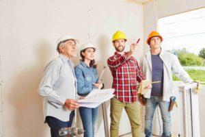 Vorarbeiter und Architekten planen zusammen Hausbau