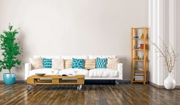 Modern_interior_of_living_room_with_white_sofa,_pallet_table,_plant_and_shelf_3d_rendering