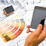 Male_Hand_holding_a_Smart_Phone;_Construction_plans_with_Color_Palette_and_Miniature_House_on_blueprints_Background;_Communication_and_Construction_Industry_Concept