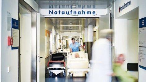 Notaufnahme_Eingang_Krankenhaus_mit_Arzt_Rollstuhl_und_Patient_in_Bewegungsunschärfe_auf_dem_Flur_und_Pfleger_mit_Krankenbett_