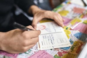 Hanoi,_Vietnam_-_26_February_2019:_man_is_writing_a_postcard_on_a_colorful_table_which_pasted_with_multicolored_cards_with_messages_in_the_cafe._Closeup._Horizontal._Editorial.