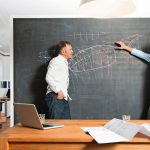 Two_businessmen_discussing_drawing_at_blackboard