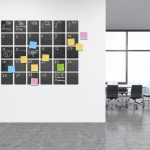 Calendar_in_modern_office_interior._Post_it_notes_on_wall._Black_board._New_York_City_view_through_big_window._3d_rendering