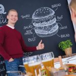 Young_and_smiled_man_at_blackboard_wall_with_menu