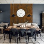 Dinner_table_in_a_retro_living_room_with_furniture_made_of_wood_and_a_big_clock_hanging_on_the_wall