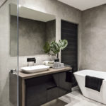 Modern_bathroom_with_a_shower_area_and_bath_tub_including_a_wall_mirror_beside_a_fancy_plant_near_a_tap_and_sink_over_the_wooden_counter_and_dark_cupboard